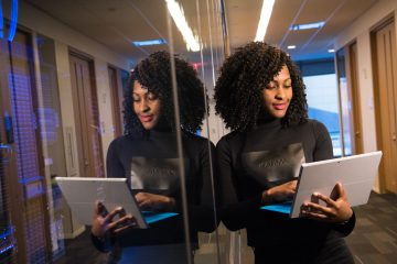 Woman standing and looking at laptop